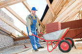 Worker roofer and wheel barrow with clay tile — Stock Photo