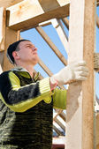Builder working with level and timber board — Stock Photo