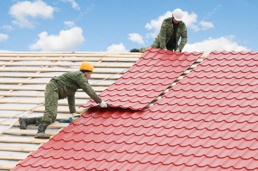 Two workers on roof at works with metal tile and roofing iron  Zdjcie stockowe #5419365
