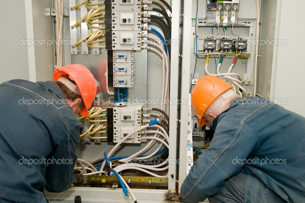 Two electricians working on a industrial panel mounting and assembling new wiring — Stock Photo #5419403