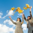 Two girls and Autumn leaves over blue sky -  