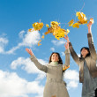 Two girls and Autumn leaves over blue sky - Stockfoto