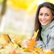 Stock Photo: Happy student girl lying in autumn leaves with netbook