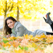 Happy student girl lying in autumn leaves with netbook - Stockfoto