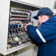 Electrician at voltage adjusting work - Stock Photo