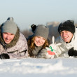 Smiling young lying in snowdrift — Stock Photo #5427983