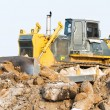 Bulldozer loader at winter frozen soil excavation works — Stock Photo