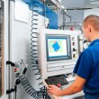 Worker operating CNC machine center - Stock Photo