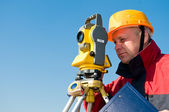 Surveyor looking at the thedolite — Stock Photo