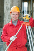 Smiling surveyor builder and level — Stock Photo