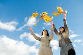 Two girls and Autumn leaves over blue sky — Stock Photo