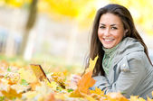 Happy student girl lying in autumn leaves with netbook — Stock Photo