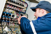 Electrician at voltage adjusting work — Stockfoto