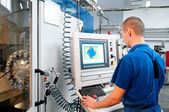 Worker operating CNC machine center — Stock Photo