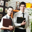 Waitress girl and waiter man in restaurant — Stock Photo
