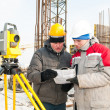 Surveying works at construction site - Stock Photo