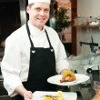 Küchenchef mit zubereiteten Speisen auf dem Teller — Stockfoto