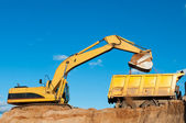 Excavator and dumper truck — Stock Photo