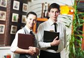 Waitress girl and waiter man in restaurant — Stock Photo