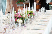 Catering table set with flowers — Stock Photo