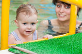 Little girl and mothe in swimming pool — Foto Stock