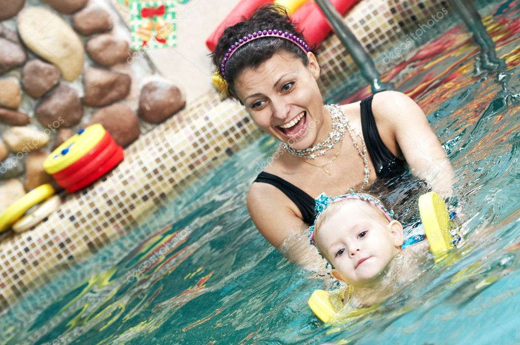 Happy smiling little girl with mother swimming at water pool — Stock Photo #5458087