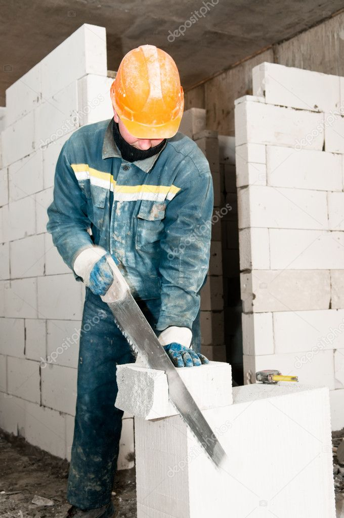 Construction mason worker bricklayer sawing off a lime sand brick — Stock Photo #5458663