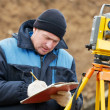 Foto Stock: Surveyor works with total station tacheometer