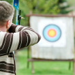 Archer aiming with bow - Stock Photo