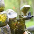 Paintball player under gunfire - Stock Photo