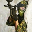 Paintball player under cover - Stock Photo