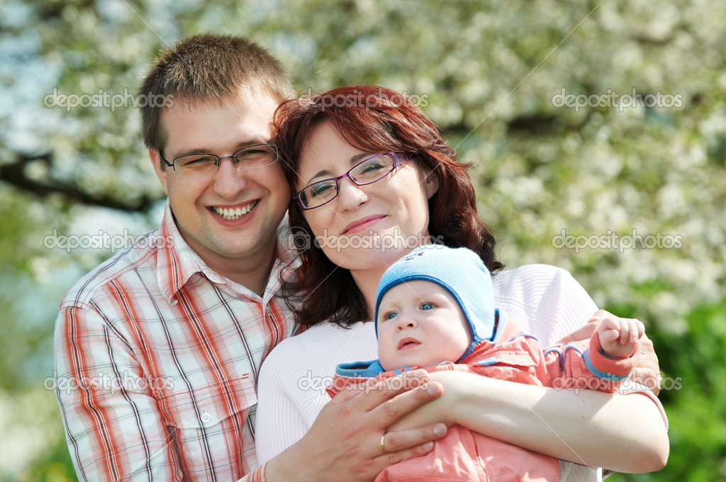 Portrait of happy three person smiling family standing outdoors over spring bloom — Stock Photo #5743869