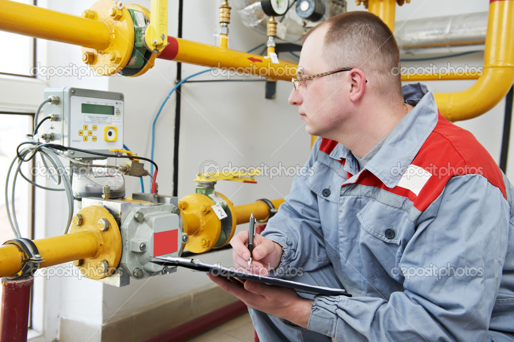 Maintenance engineer checking technical data of heating system equipment in a boiler house  Stock Photo #5745126
