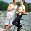 Young man and woman relaxing after jogging — Stock Photo