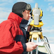 Stock Photo: Surveyor works with theodolite tacheometer