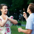 Happy couple blowing soap bubbles — Stock Photo #5913449