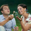 Happy couple blowing soap bubbles — Stock Photo #5913454