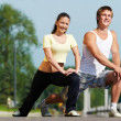 Stock Photo: Young man and woman doing stretching exercises