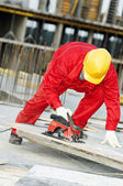 Cutting construction wood board with grinder saw — Stock Photo