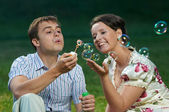 Happy couple blowing soap bubbles — Stock Photo