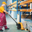 Worker with fork pallet truck — Stock Photo #5986592