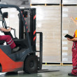 Warehouse works (forklift and workers) - Stock Photo
