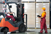 Warehouse works (forklift and workers) — Stock Photo