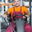 Warehouse worker in forklift loader — Stock Photo