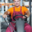 Warehouse worker in forklift loader - Stock Photo