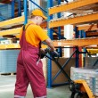 Worker with fork pallet truck — Stock Photo #5994973