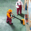 Warehouse workers with fork pallet truck stacker — ストック写真