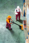 Warehouse workers with fork pallet truck stacker — Stock Photo