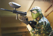 Paintball player under cover — Stock Photo