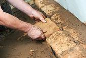 Mãos de pedreiro em obras de alvenaria — Fotografia Stock